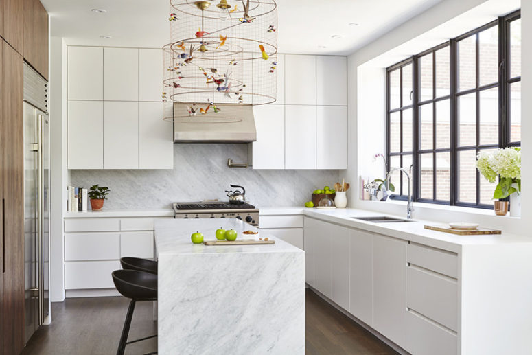 The kitchen is done with sleek white cabinets, a wooden wall with built-in appliances and marble countertops
