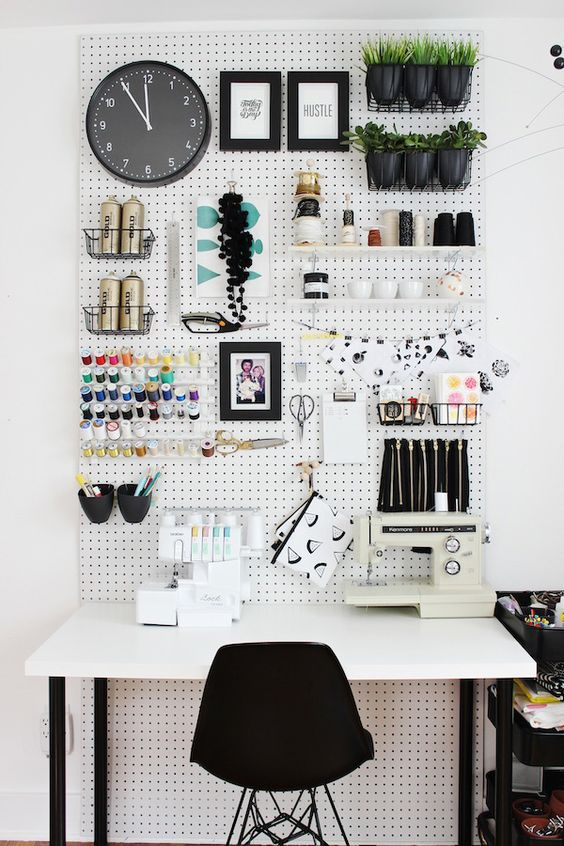 a comfy crafting nook with a large pegboard and a desk won't take much space