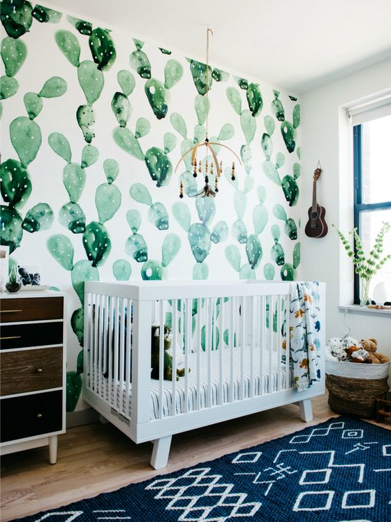 a desert-themed nursery with a watercolor cactus wall, a reclaimed wood dresser