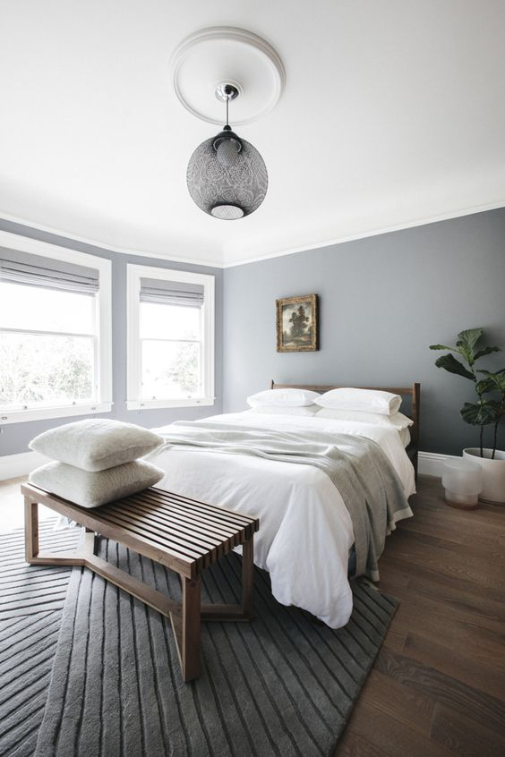 a minimalist bedroom in the shades of grey and white, a wooden bed and bench for a warmer feel