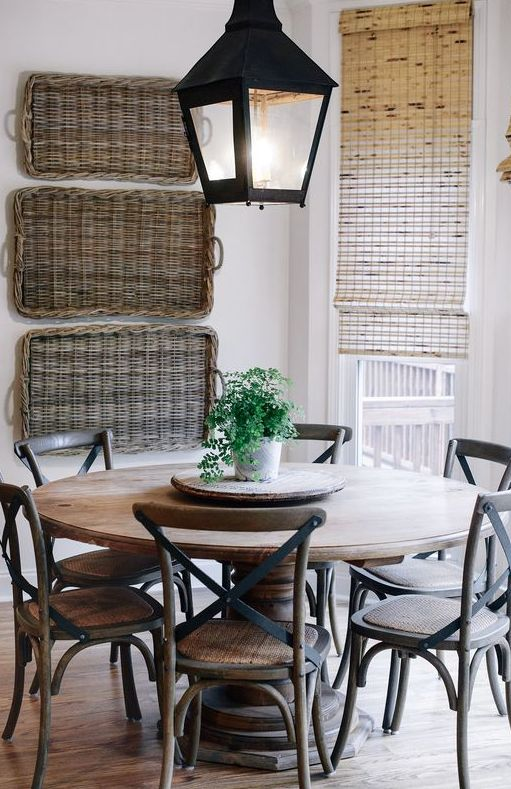 a rustic space with baskets on the wall, a wooden dining set and some neutral Roman shades