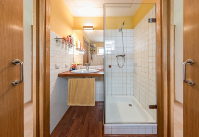 Another bathroom features a shower and a sink, the space is done with white tiles and natural wood