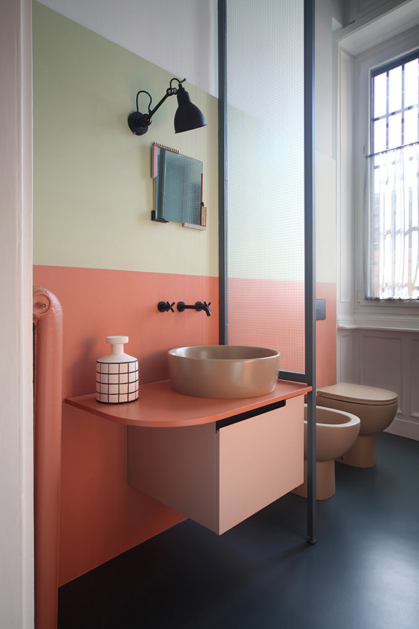 The master bathroom features a buttermlik and coral wall, a coral vanity and beige appliances