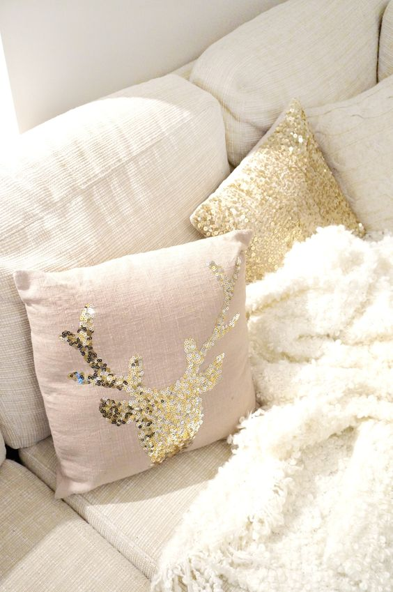 a blush pillow with a gold sequin deer is a cute idea for a woodland yet glam touch