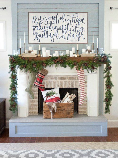a rustic mantel with an evergreen and pinecone garland, candles and a sign over it