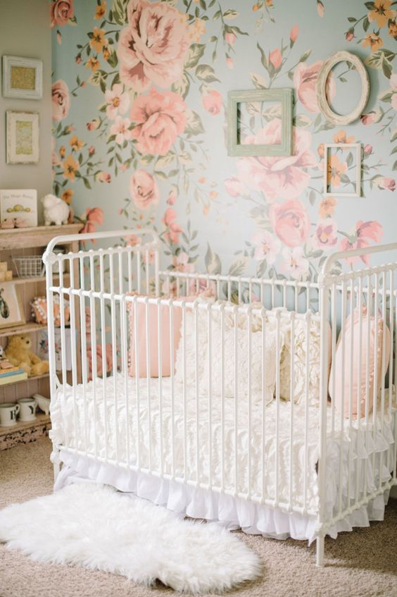 a sweet vintage inspired girl's nursery with a floral statement wall