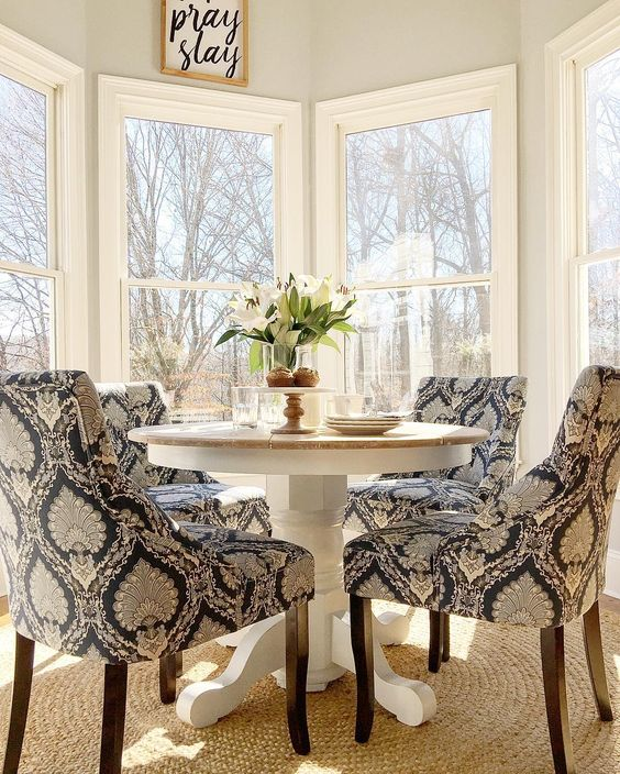 a traditional breakfast nook with a pedestal round table and printed upholstered chairs