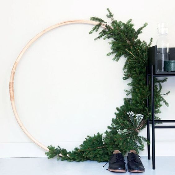 an oversized wreath with evergreens and some berries on one side looks very modern and minimalist