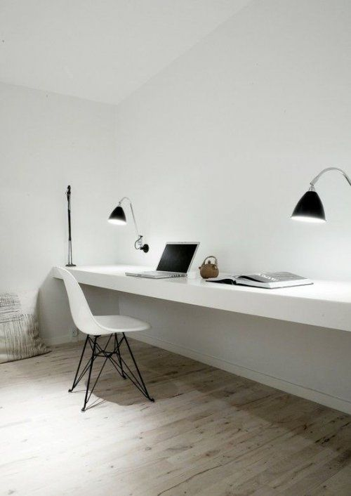 an ultra-minimalist home office with a floating double desk and black sconces