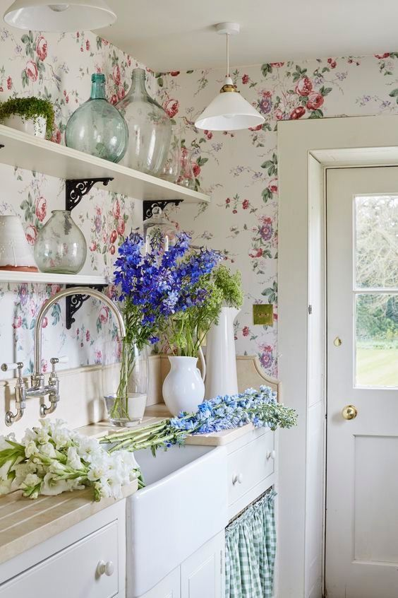 this chic light-filled ktichen is done with floral wallpaper, which makes the space cuter