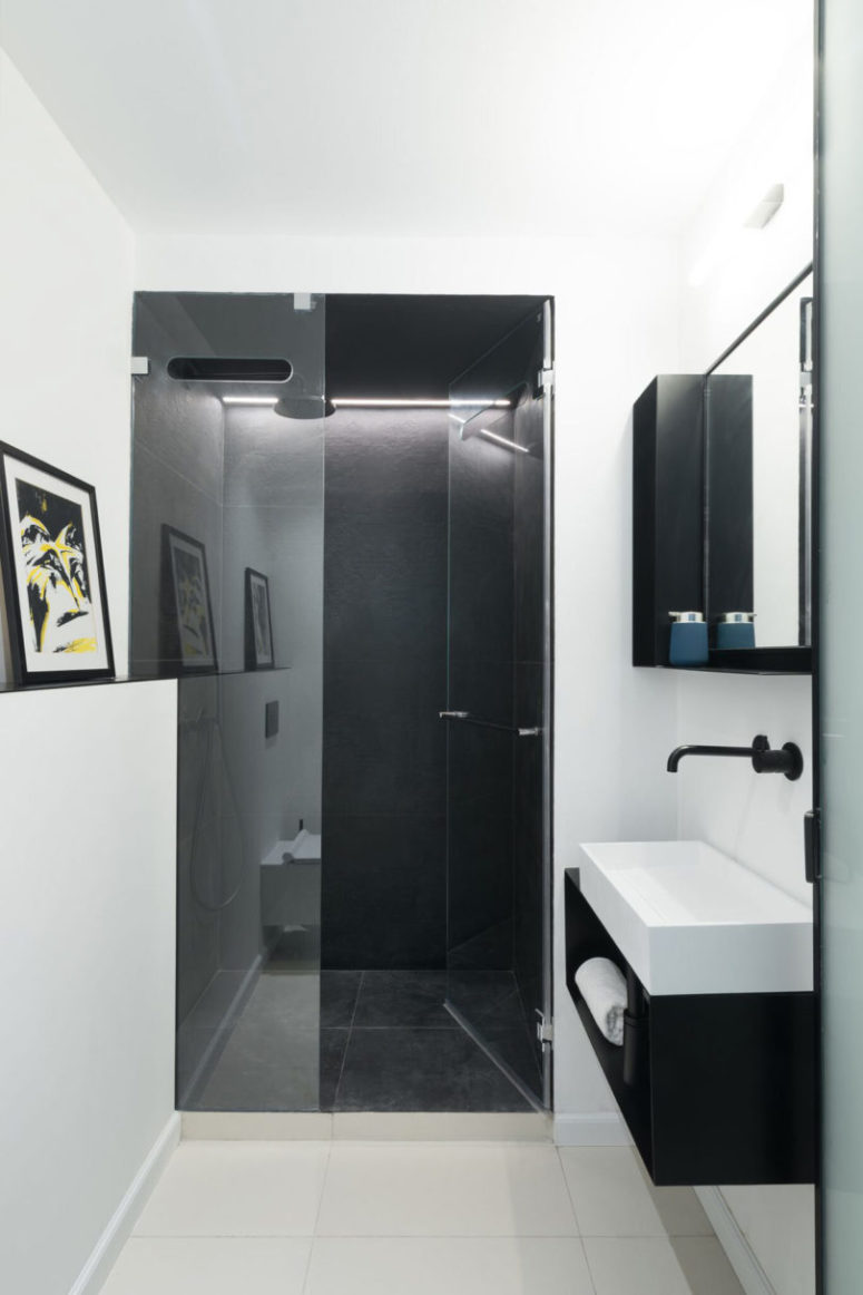 The bathroom is small, with a black tiled shower, all the rest is done in white
