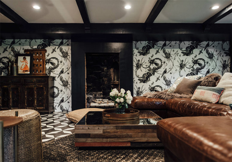 The living room is black and white, with eye-catchy wallpaper, mosaic floors and brown leather furniture