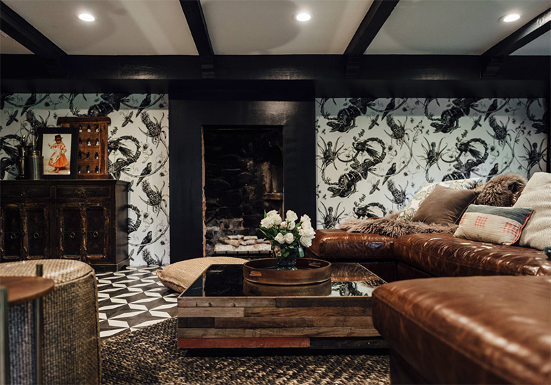The living room is black and white, with eye catchy wallpaper, mosaic floors and brown leather furniture