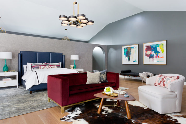 The master bedroom is done with colorful upholstered furniture, colorful artworks an creative rugs