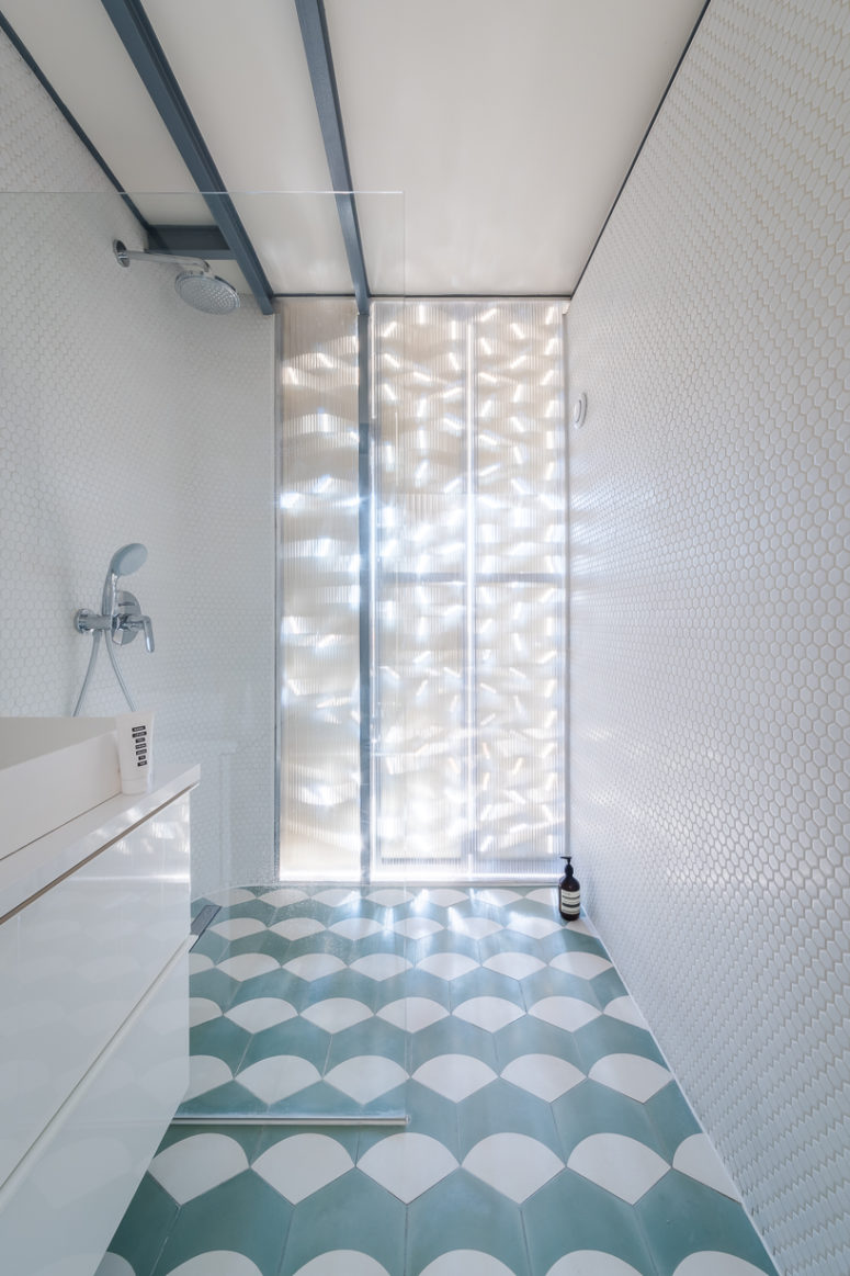 There's also an en-suite bathroom clad with white penny tiles and with a geo tiled floor