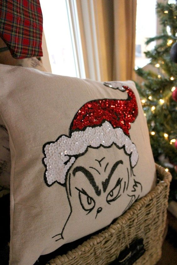 a fun Grinch pillow in red and white sequins looks super whimsy and bold and you can make it yourself