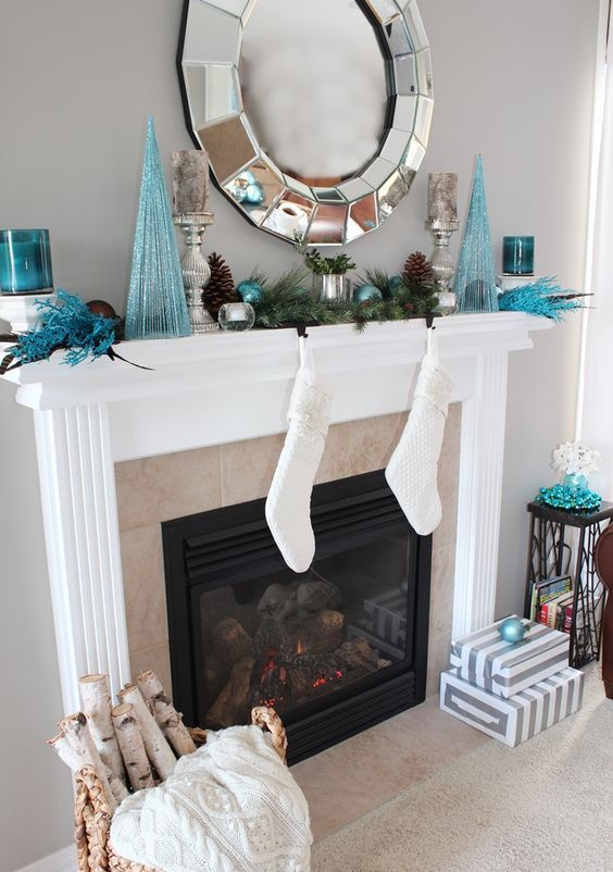 a glam mantel with a large mirror, blue trees, ornaments and candle holders and pinecones