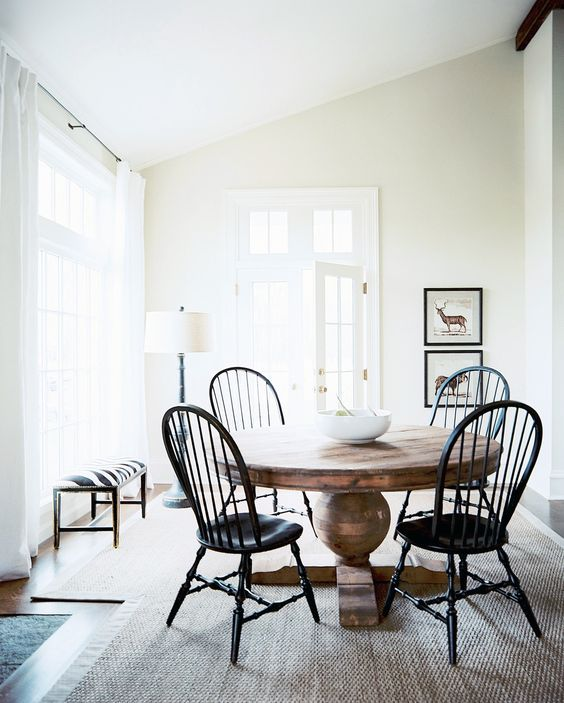 a large vintage wood pedestal table and vintage black chairs for an eye-catchy breakfast space