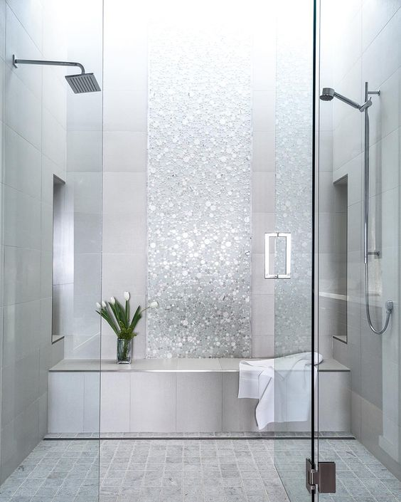 a shower and steam room done with grey tiles and shiny silver accents looks very glam and cute