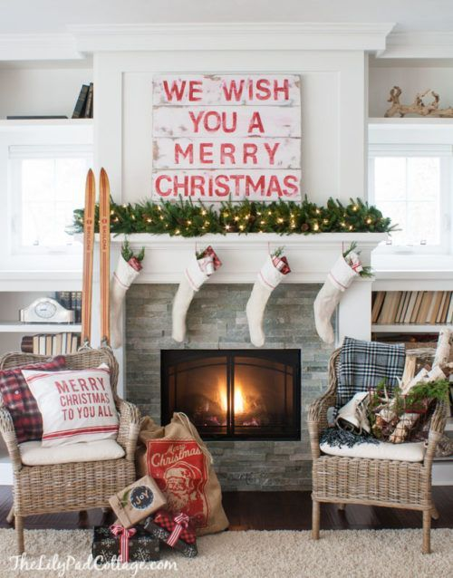 a whitewahsed pallet sign, a lush evergreen garland with lights, stockings and skis next to the fireplace
