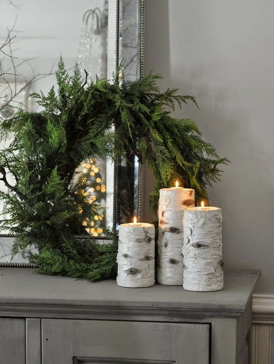 an evergreen wreath with birch branch candle holders for a rustic feel in your space