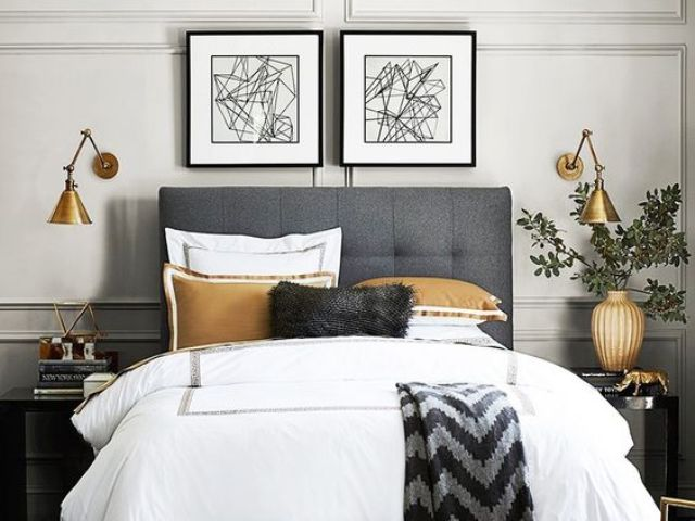 industrial brass sconces with an asymmetric shade add a cool touch to the bedroom