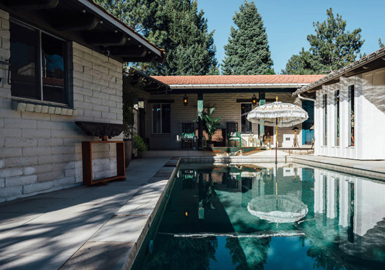 The backyard features a large swimming pool and a dining space