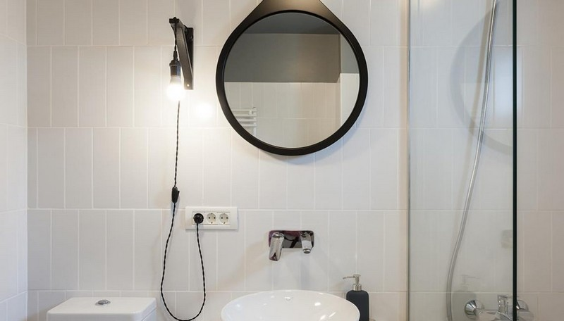 The bathroom is also monochromatic and sleek, with black touches
