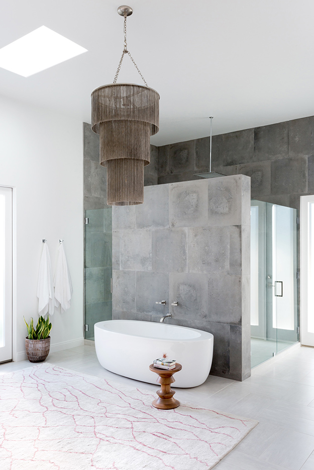 The master bathroom is done with grey stone, there's a glass shower space and a free-standing bathtub