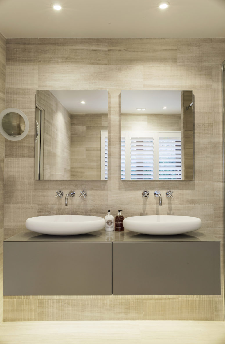The master suite's bathroom features a double sink vanity with matching wall mirrors and spotlights on the ceiling