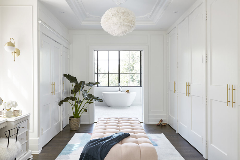 There's a large closet with a pink ottoman, all the clothes and shoes are hidden behind the doors to give the closet a neat look