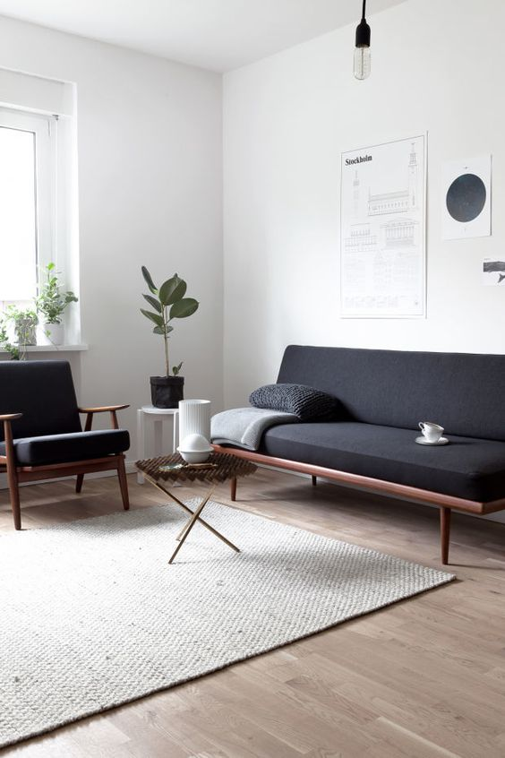 a minimalist interior with a Scandinavian feel, wood framed furniture and a jute rug