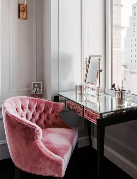 a mirror vanity and a pink velvet chair make this makeup nook very glam and cute
