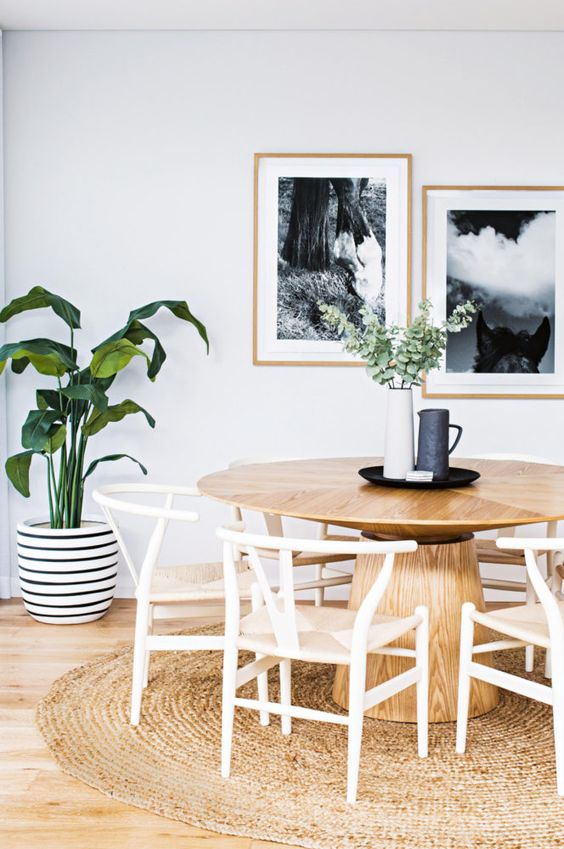 a modern breakfast nook with a simple wooden pedestal table, some chairs and a jute rug looks very natural