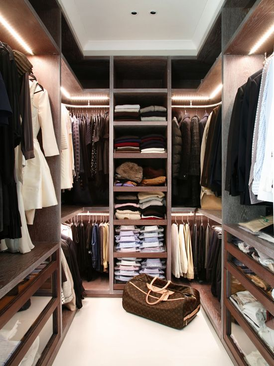 a trendy modenr closet with natural wood shelves and additional light and glass drawers