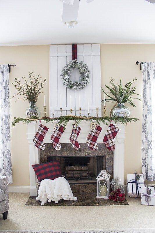 plaid stockings, an evergreen garland with wooden beads, candles in gilded candle holders and a snowy wreath over the mantel