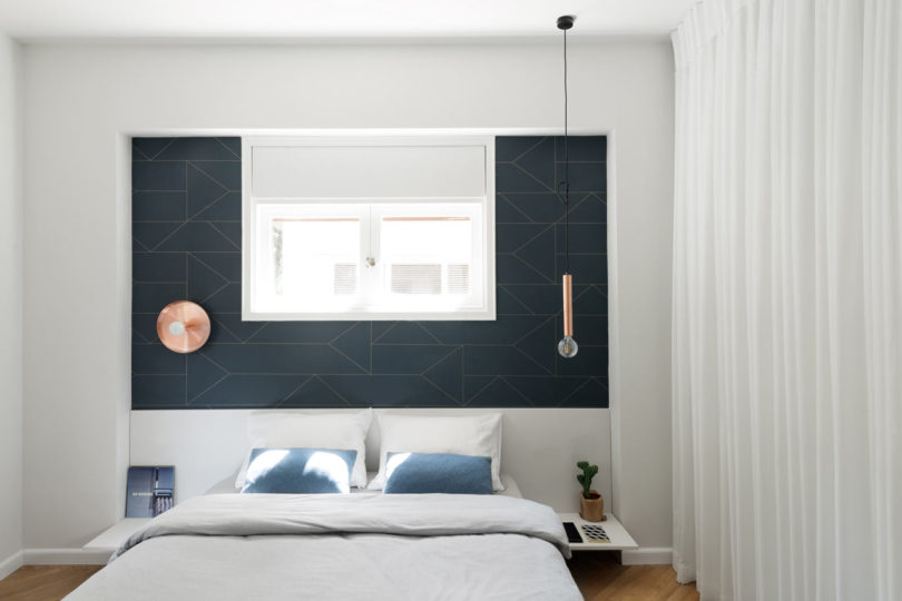 A geometric headboard wall and different lights for each side make the space cooler