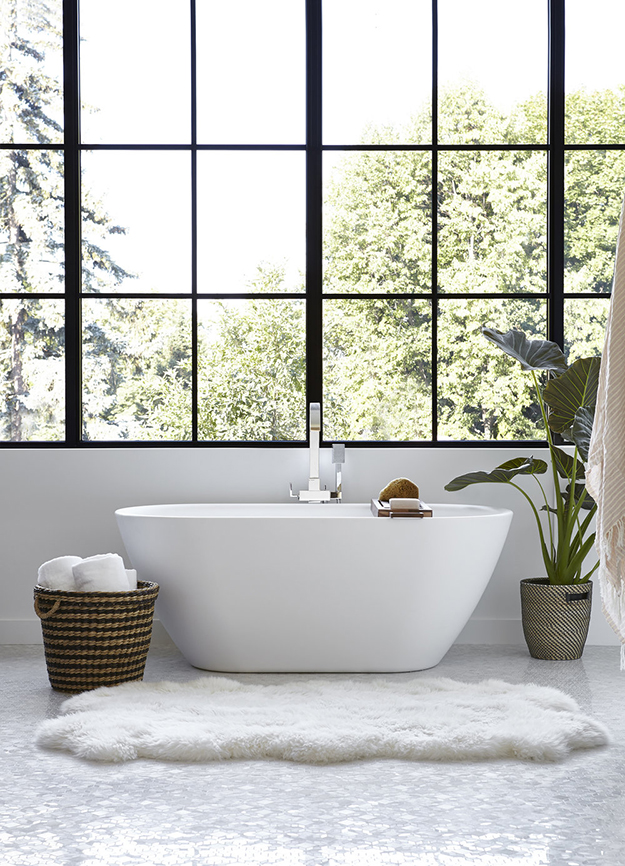 The master bathroom features a free-standing bathtub and a glazed wall for cool views