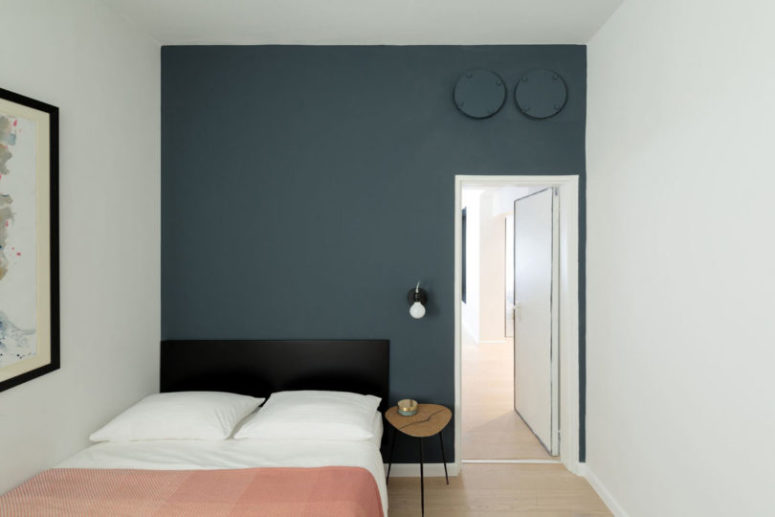 The second bedroom is done with a smoky blue statement wall, a large bed and an artwork