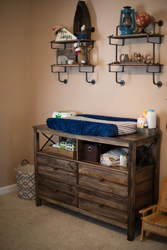 a dresser of reclaimed wood features open storage and can serve as a changing table