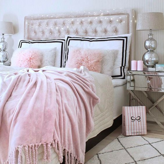 a pink velvet blanket, faux fur pillows and a creamy upholstered velvet headboard