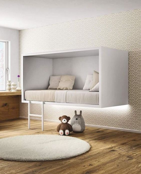 a unique white box suspended bed with a ladder for a minimalist kid's room