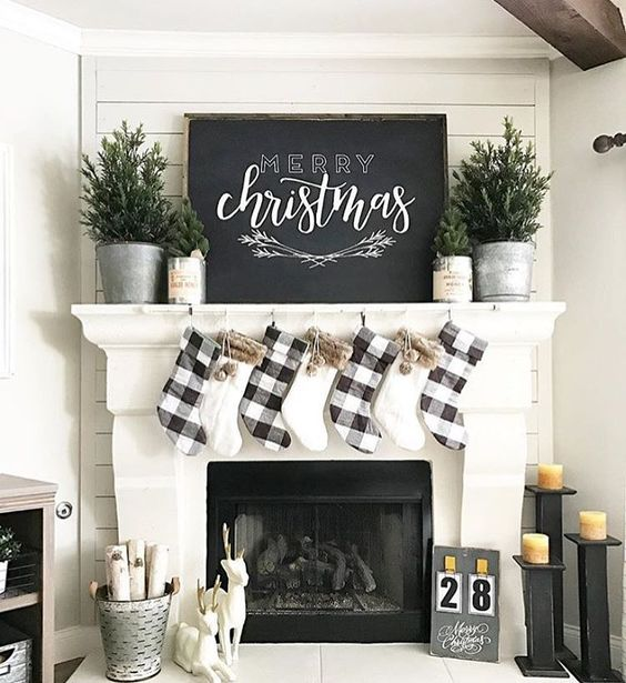 plaid and faux fur stockings, evergreen trees in pots and a large chalkboard sign for a cozy neutral look