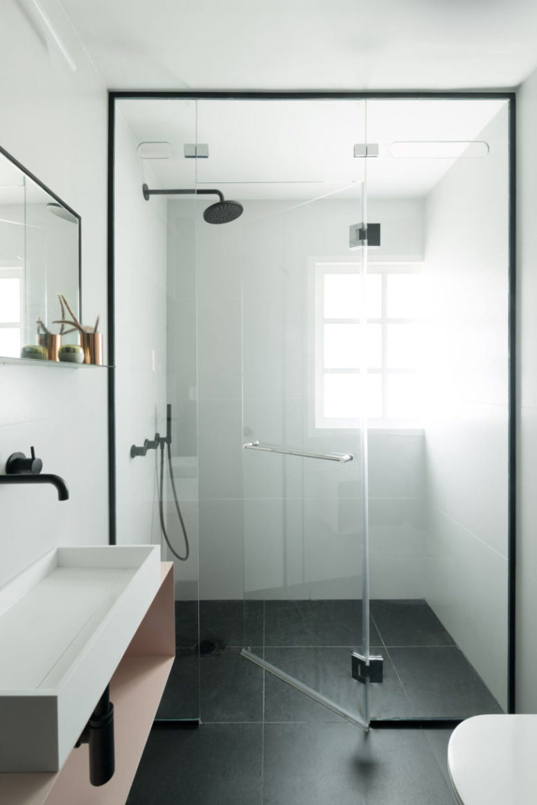 The second bathroom looks ethereal, with white tiles on the walls and black ones on the floor