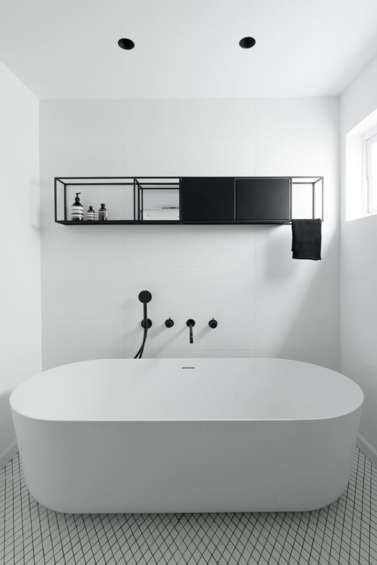There's a bathroom with a large free-standing bathtub and a hanging shelf unit for storage