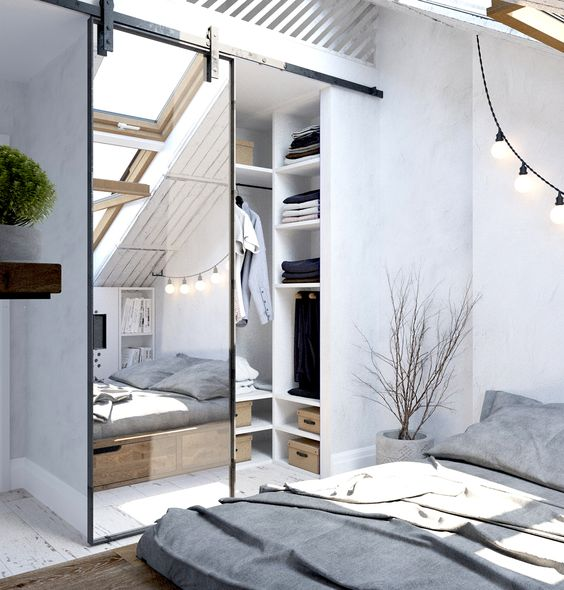 a Scandinavian bedroom with an attic closet, which is separated with a mirror barn door