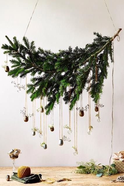 a fresh take on a Christmas wreath made of a fir branch and some little vases with greenery