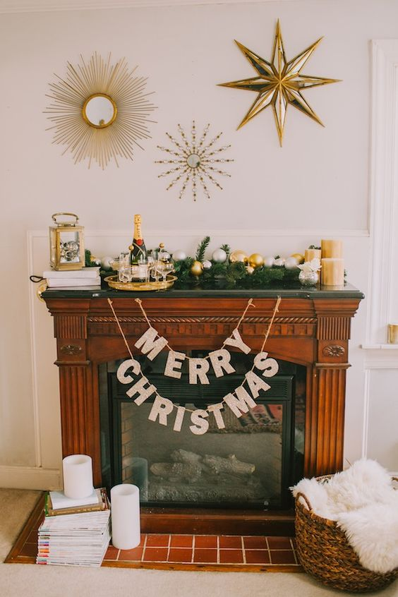 a glam mantel with shiny metallic ornaments, gold candles, a gold lantern and a champagne tray