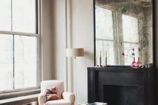 12 a large antique mirror over the fireplace and a large crystal chandelier for a refined glam space