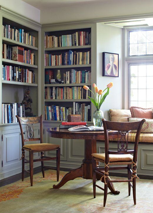 a vintage library space with a breakfast zone, vintage chairs and a pedestal table complete the look